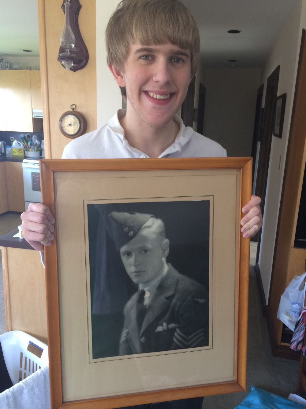 Photo of Ivan Steen Sollows– Steen Christopher Sollows holding a framed photo of his great uncle and namesake, Ivan Steen Sollows