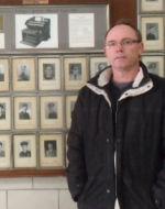 Photo of Ken Brown– Ken Brown, nephew of Donald Sutherland Bier, is seen here proudly standing beside his uncle's portrait.