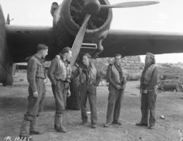 Group Photo– 21 March 1943 Canadian crew with a R.A.A.F. torpedo bomber sqn in Malta. Five members of the crew discuss the impending operation. At the extreme left is F/O Burrows, a RAF observer who sometimes flies with them, The others in the picture are L to R: F/0 Gordon Lawson, Grandview, Manitoba; F/0 A. R. Pagan, Saskatoon, Sask; F/0 McCorkell, Wakefield, Quebec, and Sgt. N.C. Rowley from London, Ontario.