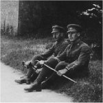 """Photo of Dudley Alan Herbert Acheson– Lt. Acheson and a companion named Ross rest along an English country road.  The 54th Battalion War Diary for  5 November, 1916, states, """"In Line. Stakes of proposed new trench checked up as much as possible but thorough inspection impossible in daytime account enemy snipers very active.  Lieut. Acheson, D.A.H., killed while going over proposed trench work with Lieut. B.S. Todd of the 87th Canadian Inf. Bn, who was also killed.  Enemy artillery active in afternoon.  The Battalion was relieved by the 87th Canadian Inf. Bn., relief being completed by 8 p.m.    Private collection"""