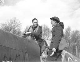 "Group Photo– 19 March 1943 412 Canadian Squadron, returning from a sweep over enemy territory, F/O L.W. ""Pip"" Powell, D.F.C., train-busting ace from Edmonton, Alta., describes to one of the ground crew, LAC W. Coutts, Melfort, Sask., how he and other members of the squadron raked a convoy with cannon fire."