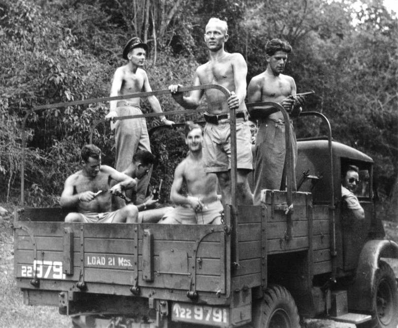 """Group Photo– Members of two RCAF Liberator crews preparing for a shooting expedition in Ceylon in late May or early June 1945.  Of the eight RCAF crewmen of Liberator KH326 who failed to return from an RAF 357 Squadron Special Duties operation on 6 June 1945 (supply drop to Force 136 operatives behind Japanese lines), three are seen here:  J/12779 Flight Lieutenant Arie Frank TIMMERMANS:  Captain of the aircraft (pilot).  Age 28, son of Frank Joseph and Maude Gladys Timmermans of Blind River, Ontario; husband of Mary Constance Timmermans (nee Galashan), of Burlington, Ontario.  He is the tall blonde standing & facing the camera.   J/47871 Flying Officer William Peter MCLEOD:  Wireless Op/Air Gunner.  Age 23, from Claresholm, Alberta.  He is standing to the left of Timmermans, looking to the right and wearing an officer's cap.  J/47869 Flying Officer George FAULKNER:  Wireless Op/Air Gunner.  Age 22, from Victoria, British Columbia.  Looking down at a pistol in his hands, he is standing to the right of Timmermans.  Sitting in the cab of the truck, with sunglasses is RCAF C.1490 S/Ldr O.A.H. """"Haig"""" SIMS, pilot & Commanding Officer of the 357 Sqn detachment sent to Ceylon in late May '45.   In 1955, during the Malayan Emergency, the wreck of the Timmermans crew's Liberator, KH326, was discovered in deep, rugged jungle by the Royal Scots Fusiliers while on a war patrol in search of Communist guerrillas.  Although no human remains were found in a brief search, most of the supplies from 1945 were still intact in drop containers within the fuselage or scattered nearby, undisturbed since 6 June 1945.  After a clearing was prepared by the Fusiliers, Royal Navy helicopters were used to remove many guns, ammo, and other supplies, to prevent them falling into the hands of the Communists after the patrol moved on.  In 2010 the wreckage was finally rediscovered."""