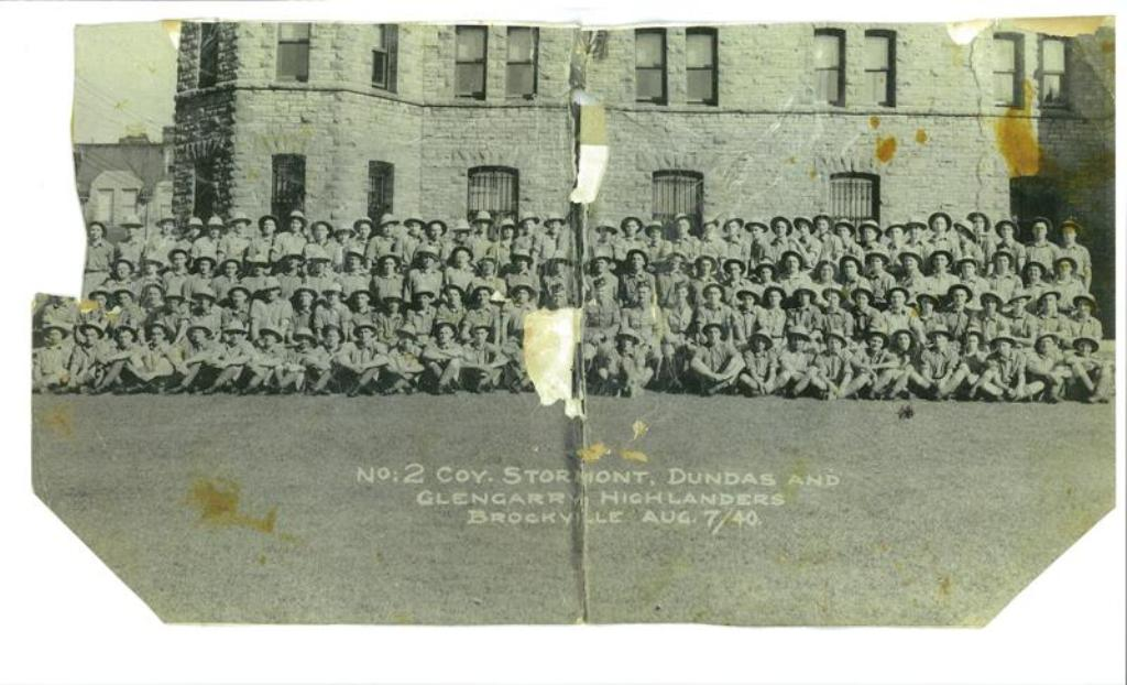 Group Photo– This is a photograph of Sergeant Clarence Arthur Gibson's (C53903) No:2 Company the Stormont, Dundas And Glengarry Highlanders taken August 7th 1940 in front of the Brockville Armouries before being deployed overseas. Sergeant Gibson is pictured on the far right side of this photograph front row, just above the small black mark.