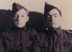 """Group Photo– John M. Simpson (R) and brother William J. Simpson (L) c. 1940  John (Jack) was 20 yrs. old and a Rifleman with the QOR of C, William (Red) was 15 yrs old and a Private with the Kent Regt when this photo was taken. Four years later they went ashore together with the QOR of C at Juno Beach on D-Day. William said that John's last words as he died were """"Keep Going!"""" William died in the line of duty as a City of Toronto Firefighter in 1966."""