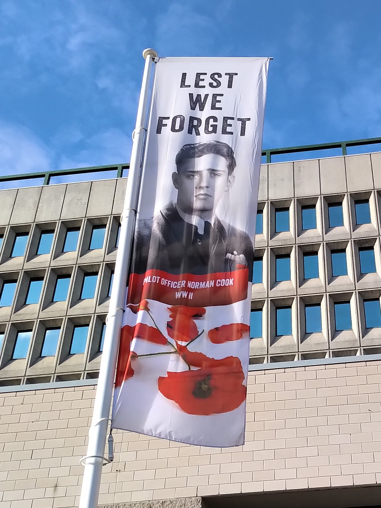 Memorial– Yearly in Barrie, Ontario, in about October and November, banners commemorating local war dead are displayed.  Pictured here is a banner in memory of Pilot Officer Norman Cook.  (Image taken by Gregory J. Barker of Barrie, Ontario, in 2020.)