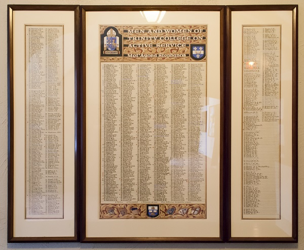 """Memorial Scroll– This framed illuminated scroll, written in calligraphy, is entitled """"Men and Women of Trinity College on Active Service. Met'Agona Stephanos"""". It hangs in the hallway outside the narthex of the chapel at Trinity College in the University of Toronto. Small symbols beside the names indicate men and women who are fallen, decorated, and prisoner of war. The list of names includes: '38 Kerby, H.W.  Photo: Cody Gagnon, courtesy of Alumni Relations."""