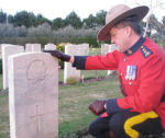 Paying respects– Superintendent Greg Peters of the RCMP at the gravesite of Gordan Evan Bondurant.