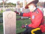 Paying respects– Superintendent Greg Peters of the RCMP at the gravesite of Terence Graham Newcomen Watts.
