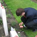 Photo 2 of Adnan Saciragic– Youth Delegate Adnan Saciragic gently sprinkles some soil from PEI on the grave of John Archibald MacLaren in Holten Canadian War Cemetery.