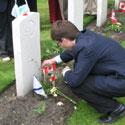 Photo 3 of Adnan Saciragic– Youth Delegate Adnan Saciragic places a Canadian flag on the grave of John Archibald MacLaren in Holten Canadian War Cemetery.