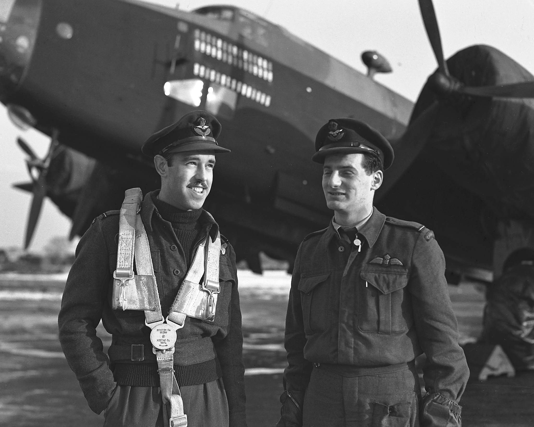 """Group Photo– PL-41811 - 16 Dec 1944, United Kingdom Two members of 432 """"Leaside"""" Squadron RCAF with more than 20 operations against the enemy to their credit. (Right) Flight Officer Mike Krakovsky, Toronto, pilot and Flying Officer Gordon Wilson, Chatham (286 Lacroix St.) bomb aimer."""