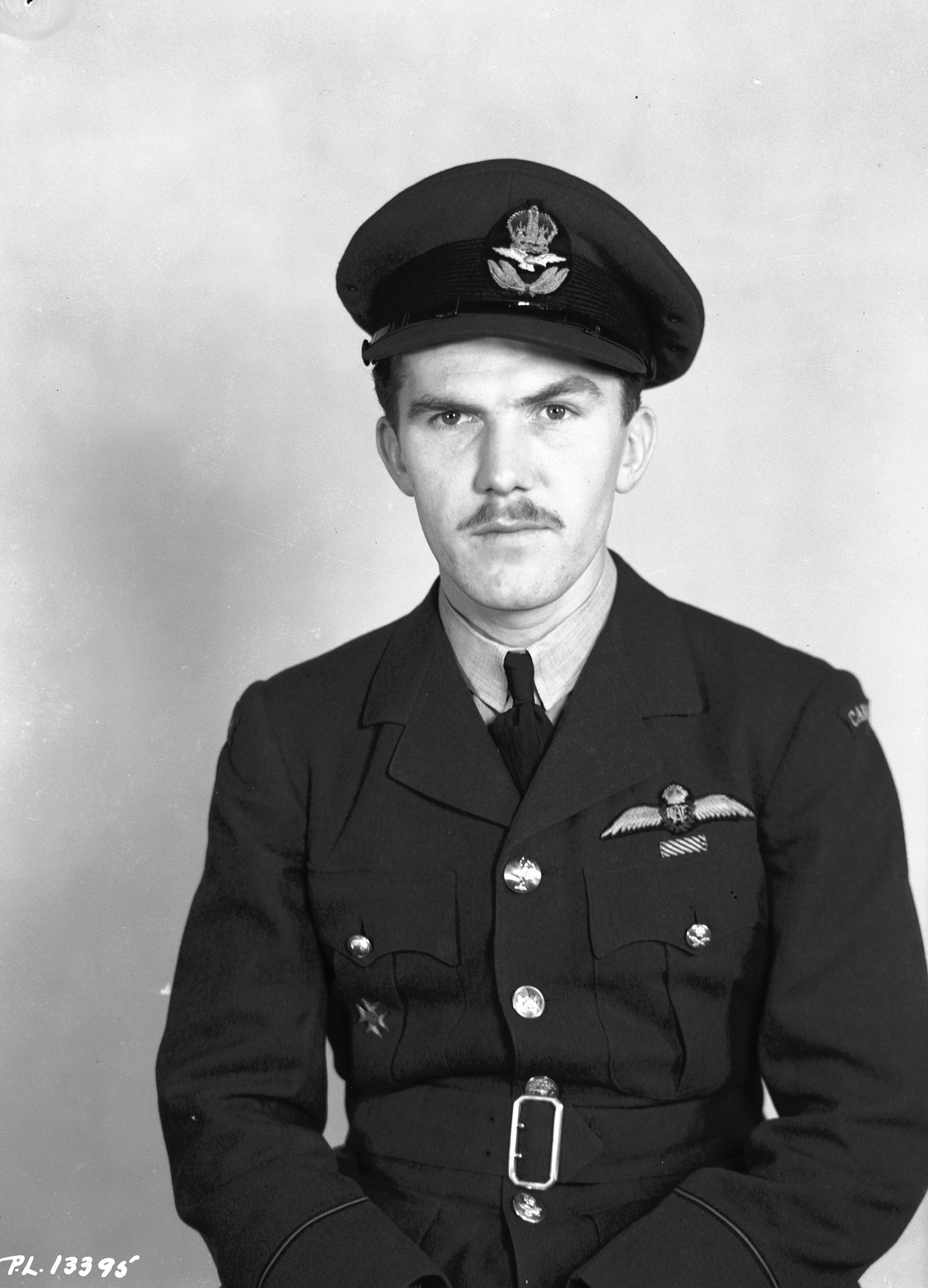 """Photo of James Ballantyne– PL-13395 - 6 March 1943 - Portrait: Pilot Officer J.H. Ballantyne, J/16085, Toronto, Ont. Pilot Officer James Hamilton Ballantyne, D.F.M. of Toronto who won the Distinguished Flying Medal while he was a flight sergeant serving with the Royal Air Force in the defense of Malta. Son of Mr. and Mrs. J.H.H. Ballantyne, 43 Hendrich avenue, Pilot Officer Ballantyne has destroyed at least five enemy aircraft and damaged others and his citation notes that he """"is a most courageous and brave fighter pilot, who has played a worthy part in the defense of Malta."""""""