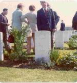 Photo of Leigh McBride– Leigh McBride behind his brother Ken's gravestone at Coriano Ridge in 1974.