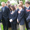 Photo 3 of Amanda White– Youth Delegates pause for a moment of silence in memory of Frederick Hutchinson Behie, following Mandy White¿s presentation in Groesbeek Canadian War Cemetery.