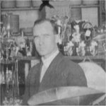 Photo of Norman Riddell Rogers– Norman Riddell Rogers, age 29 (1915), in his father's store on King St. in Gananoque, Ontario