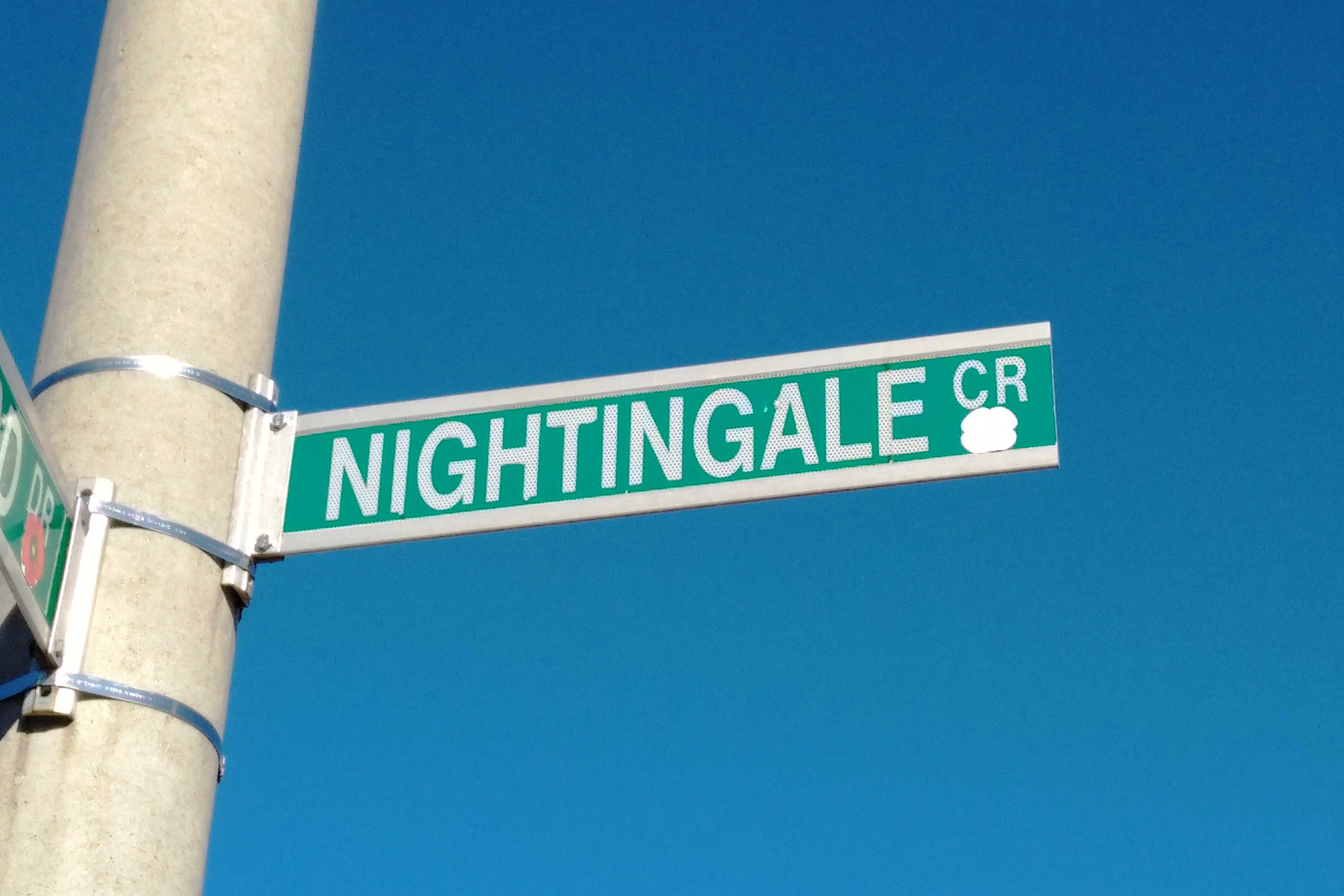 Memorial– Street sign on Nightingale Crescent in Barrie, Ontario.  This street was named in memory of Ordinary Seaman W.J. Nightingale, RNCVR.  (Image taken by Gregory J. Barker of Barrie, Ontario, in 2018.  Submitted by Navy League Cadet Corps CHAMBLY, Barrie, Ontario.)