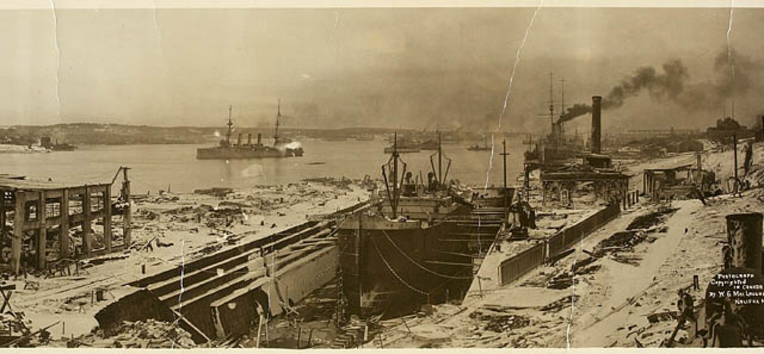Halifax Harbour– A view of Halifax Harbour – shortly after the 6 December 1917 explosion that killed some 2,000 people and injured 9,000. Carl Cecil Wilson's ship, HMCS Niobe, can be seen making smoke, beside the tall chimney on the right.