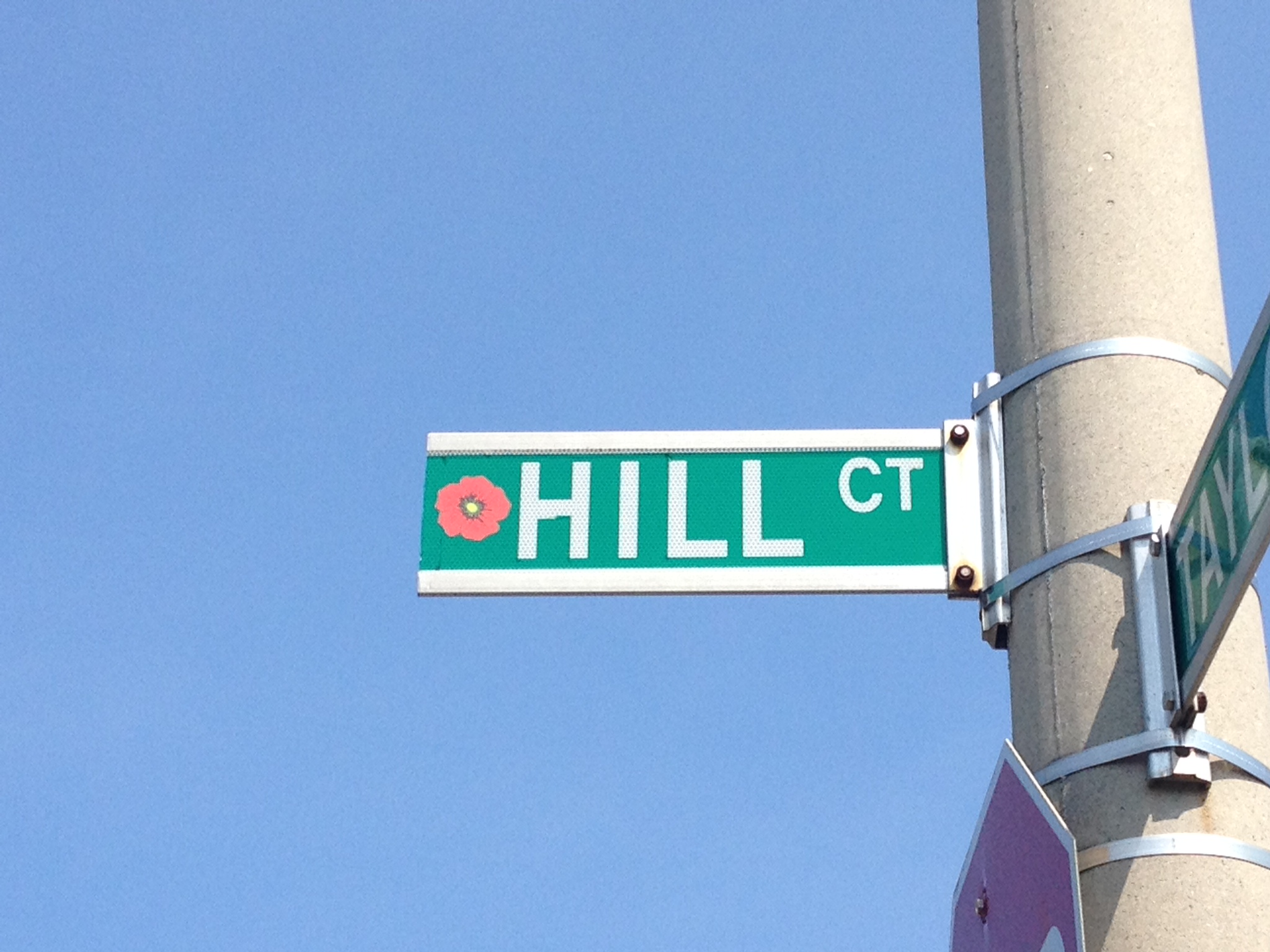 Street sign– Barrie street named in honour of Private William Earl Hill with a poppy.