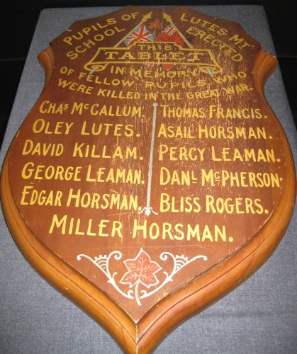 """Memorial Plaque– Plaque of brown wood, lettering is in gold.   At the top there is a union jack and a red ensign flag, at the bottom there is a maple leaf. This plaque hung in the Second Baptist Church of Lutes Mountain (Lutes Mountain United Baptist Church) and currently hangs in the schoolroom of the Lutz Mountain Heritage Museum. Memorial Inscription:  Marked in gold lettering: """"Pupils of Lutes Mt. School erected this tablet in memory of Fellow Pupils who were killed in the Great War."""" Chas. McCallum Thomas Francis Oley Lutes Asail Horsman David Killam Percy Leaman George Leaman Danl. McPherson Edgar Horsman Bliss Rogers Miller Horsman."""