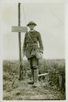 Photo of Frederick George Scott– Canon Frederick George Scott, standing at the grave of his son, Henry Hutton Scott. Canon Scott found his body where he fell near Regina Trench and he carried his son`s body to safety and personally made the wooden cross in this photo.
