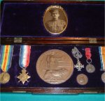 "Medals and Memorabilia– The medals and memorabilia of Cpl. Harry Jordan Guest. Mounted in a period oak-box is the 1914-15 Star ""Trio"", Memorial Plaque, and Memorial Cross on chain. In addition are two Good Conduct medals awarded to young Harry by the Toronto School Board after the turn of the century. A beautiful photo of Harry Guest tops the collection, showing him sometime after enlistment into the CEF. Circumstance of death reports of September 11, 1916: ""Whilst in charge of a bombing party in an advanced post at Courcelette, he was killed by the explosion of an enemy shell""."