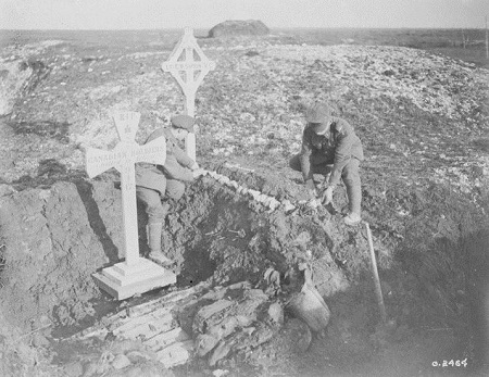 Grave Marker– Two comrades of the late L/Sergt. E.W. Sifton, V.C., 18th Battalion, visit his grave. February, 1918. Library and Archives Canada/PA-002415.  This view shows two temporary crosses, with Sifton's grave being cared for by soldiers. Ellis W. Sifton, was acting as a Lance-Sergeant in the 18th Canadian Infantry Battalion on 9 April, 1917, on the first day of Vimy Ridge operations. He was posthumously awarded the Victoria Cross for single-handedly overwhelming a German Machine-Gun position that was holding up his company. He was killed moments later.
