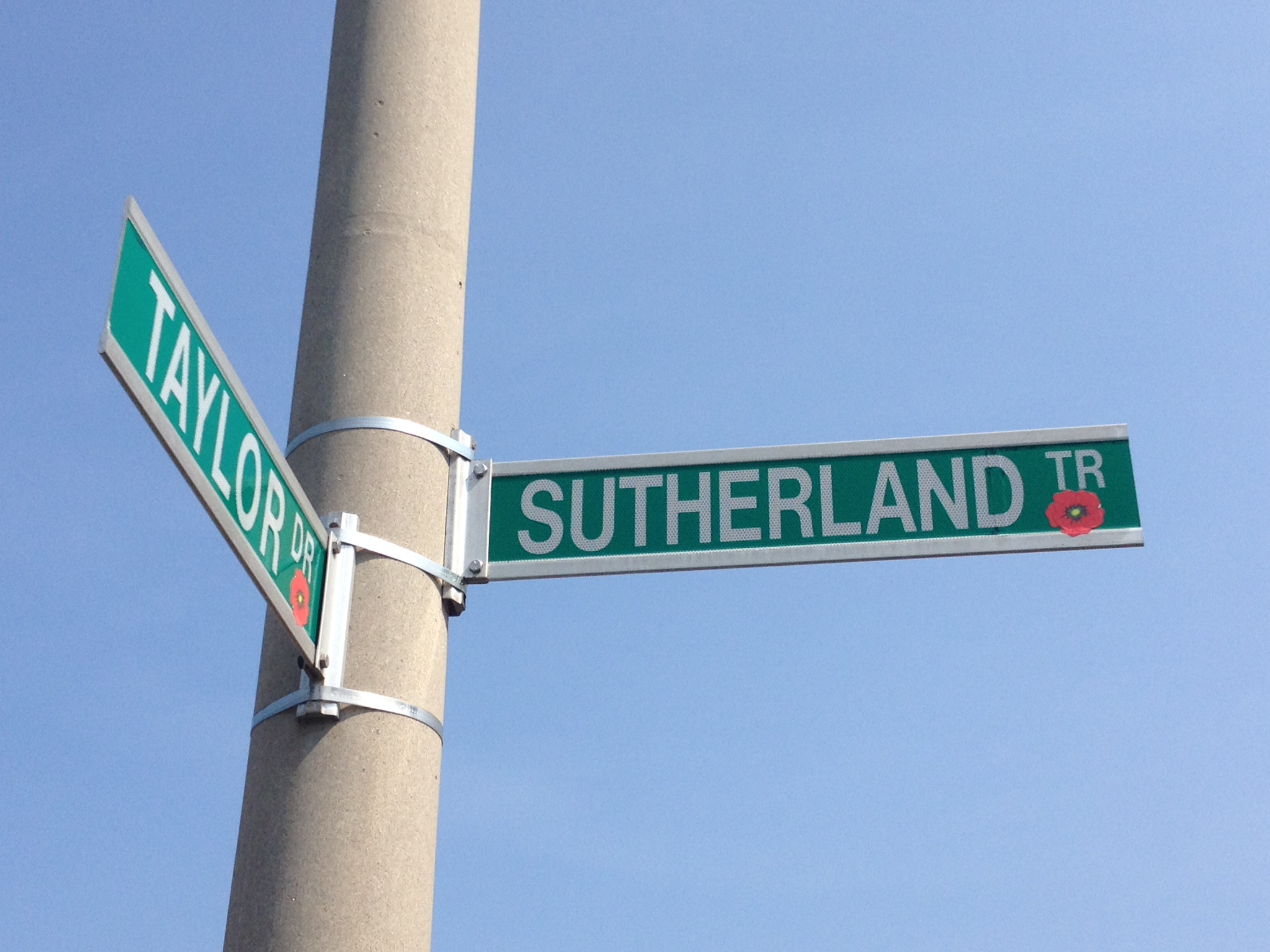 Street sign– Barrie street named in honour of Private James George Sutherland with a poppy.