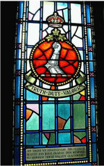 Stained Glass Window– On their 50th anniversary the class of August 1915 at the Royal Military College of Canada have placed this memorial stained glass window to honour their fallen classmates.  969 Lieut Reginald Waring Lindsay Crawford (RMC 1914) was the only son of Frederick Lindsay Crawford and Harriet Clarke Penfold Crawford, of Montreal, Quebec. He served with the Royal Field Artillery Division: C Battery 63rd Brigade. He died on July 13, 1916. He was buried in the Abbreville Cemetery, Somme, France.
