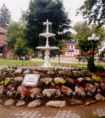 """Park– WAR MONUMENTS PROJECT """"We Will Remember"""" Industry Dept. project online  """"Bracebridge, Ontario  The Town of Bracebridge established a Park in June 1900 as a Memorial to Fred Wasdell and James Findlay who had been killed at Paardeberg, South Africa in the Boer War. Property was purchased and added to the market lots, which the Town already owned. The stables and other buildings were removed, grass was planted and the fountain was installed, but never connected to a water supply. Later a bandstand was built and symbolic cannons were placed. Mr. Thomas used a balance of the concert funds and his own money to put a plaque on the bandshell commemorating Mr. Wasdell and Mr. Findlay.  In 1959 when a Cenotaph was erected, the fountain was moved to Kelvin Grove Park. In June 1969, Council gave Brenda Cox, Thomas' granddaughter, permission to take the fountain, which was deteriorating, to her home. She gave the fountain to the newly restored Woodchester Villa in 1980. With the cooperation of the Historical Society and Town Council, the fountain has been restored to a suitable location in the Park close to where it started out 100 years ago.   The fountain was officially rededicated on July 1, 2000"""""""