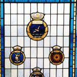 Memorial– This Stained Glass Window at the Shearwater Aviation Museum in 12 Wing Canadian Forces Base Shearwater includes four badges: HMCS Shearwater, HMCS Warrior, HMCS Magnificent, and HMCS Bonaventure. The caption states: 1945 Fifty years of Naval Air 1995 For those in peril on the sea