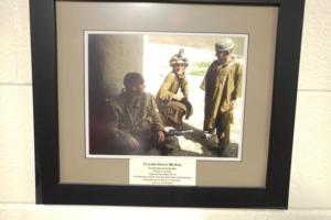 Memorial– A picture, donated by Private McKay's family, on display in the library of Eastview Secondary School, Barrie, Ontario.  It shows Pte McKay chatting with two Afghan boys, while letting one try on his helmet.  (Image taken by Gregory J. Barker of Barrie, Ontario, in 2018.)