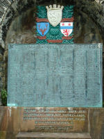 "Memorial– The Clan MacRae Honour Roll, located at Eilean Donan Castle, the home of the Clan Macrae, near the town of Dornie on Loch Duich in Western Scotland; listing Lieutenant Colonel McCrae's name (column 5, 14th name from bottom) and including a quote from his poem ""In Flanders Fields."""