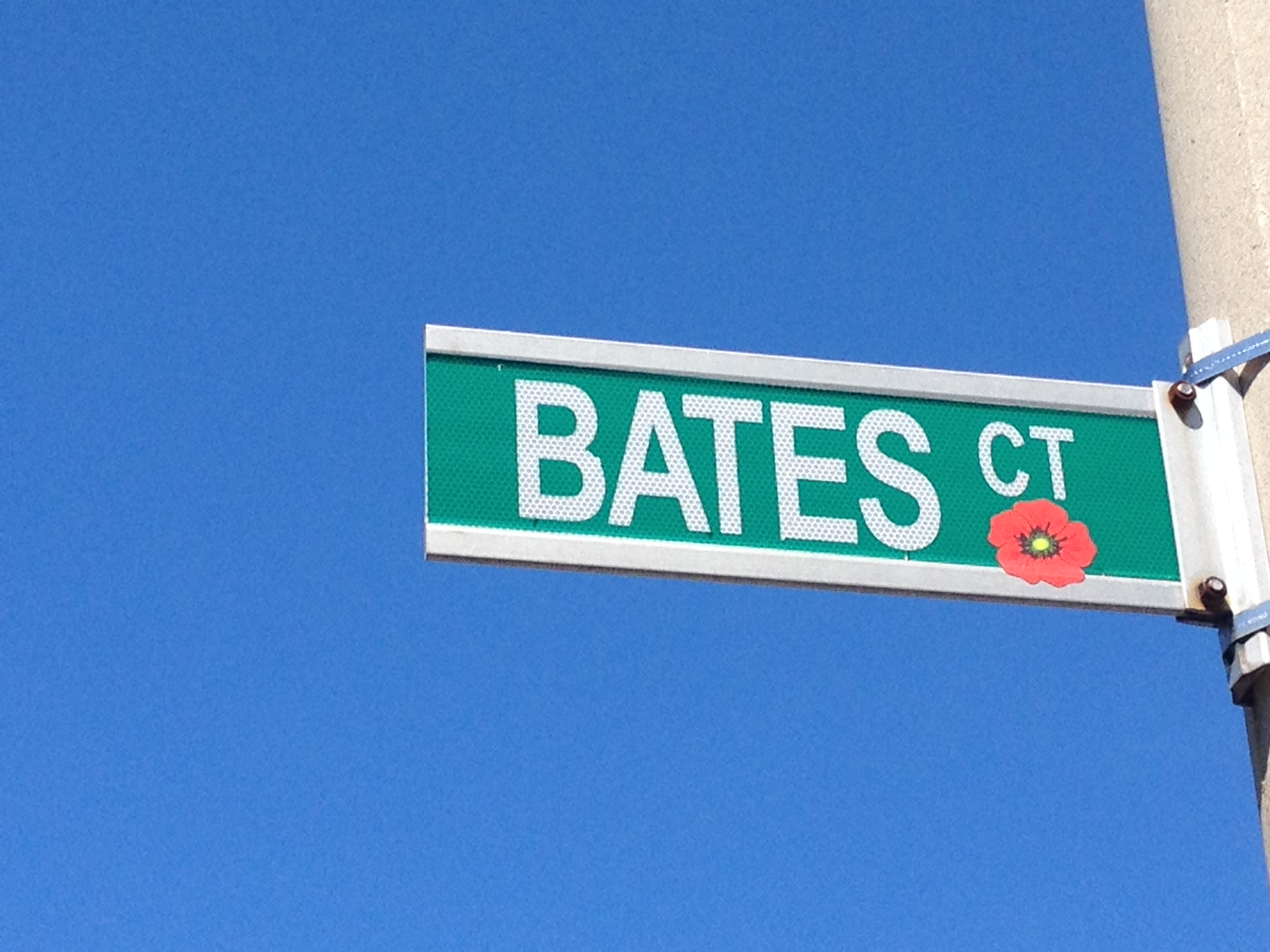 Street sign– Barrie street named in honour of Private Thomas Bates with a poppy.