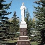 The Nanton Cenotaph– In 1926 Albert J. Hart was commissioned to create a memorial to honour the memory of those Nanton and District citizens who were killed in action during World War I. The 6.5¿¿ high statue is of Carara Italian marble and features a soldier at rest, with arms reversed in the position that would have been assumed at the burial of a comrade. It rests on a pedestal of B.C. granite. Plaques list the names of those who did not return from both wars. As well, there is a plaque honouring those who served in the Korean War. The location originally chosen for the cenotaph was next to the sidewalk that linked Shaw Street, Nanton's main street, and the Canadian Pacific Railway Station. This was most appropriate as the railway was well used at the time and hundreds of residents and visitors alike would pass the silent soldier during a day. The cenotaph was unveiled August 13, 1927 by the Earl of Haddington. Mayor J.T. Cooper presided over the ceremonies and R.B. Bennett, who would go on to become the Prime Minister of Canada, gave the principal address. Annual Remembrance Day Services have been held at the cenotaph ever since. With the closure of the railway station and the transformation of Railway Avenue into a major highway, the cenotaph's location became less and less appropriate during the latter half of the twentieth century. With the co-operation of Nanton's No. 80 Branch, Royal Canadian Legion, the Town of Nanton, and the Nanton Lancaster Society the cenotaph was carefully dismantled and the statue cleaned. It was then re-erected in Centennial Park at the entrance to the air museum in time for the 2001 Remembrance Day Service. 